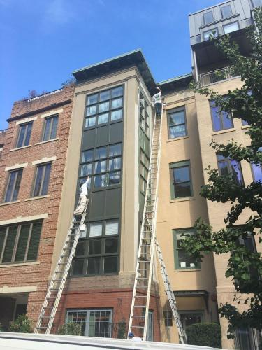 Painting green with painter working on front middle of building